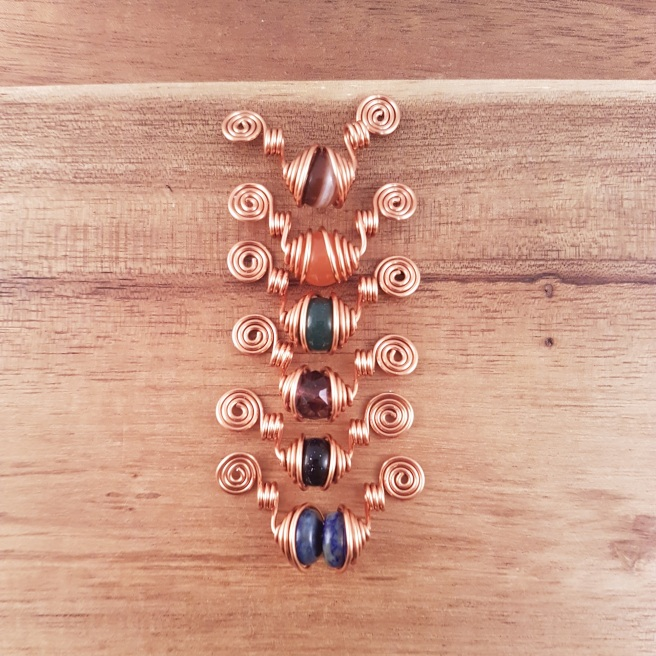 Stack of 6 copper spiral pendants with different beads in the middle